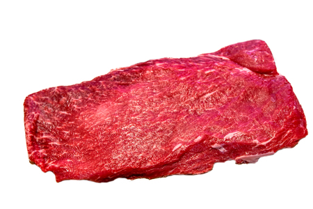 The flat iron steak lies on a white background. Insulated Reklamní fotografie - 63540522