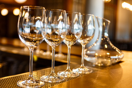 A few empty glasses and a decanter of wine stand on the bar. Stock Photo