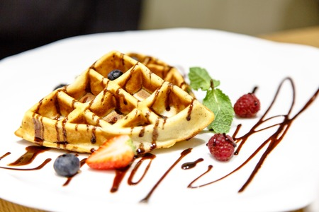 viennese: Viennese waffles drizzled with chocolate sauce with berries on a white plate. Not isolated! Stock Photo