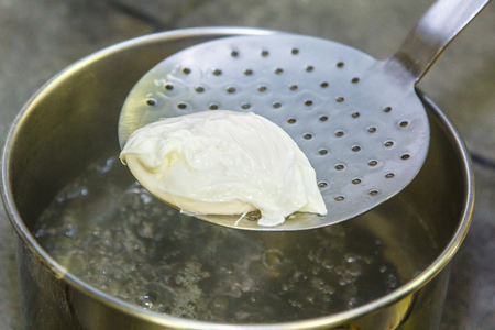Cooking poached eggs. The egg is pulled out of the water with a slotted spoon.