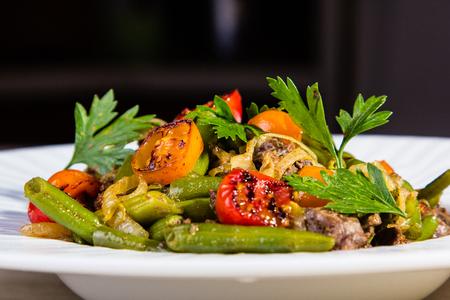 carnes y verduras: carnes y verduras (tomates, judías, cebolla a la parrilla) están en la placa