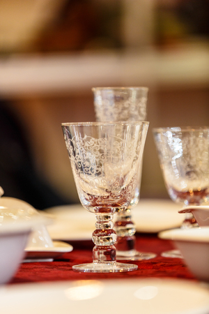 Glasses made of crystal with engraving and intricate designs are on the table. Most likely they are used to strong alcohol - Russian vodka.