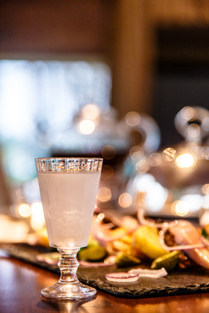 frozen glass: Russian vodka is poured into a frozen glass. Evening, gala dinner. One of the traditional ways of supply of vodka in frozen glasses. Stock Photo