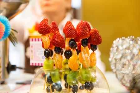 brochetas de frutas: Bayas y frutas: fresas, mandarinas, uvas y kiwi en pinchos. Foto de archivo