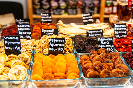Dried fruits (apricot, plum, cherry, and others) and nuts are in trays on the market. On the plates in Russian written names and prices in rubles.