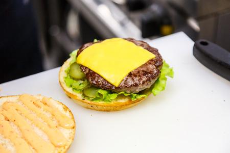 The cook prepares the hamburgers in the kitchen. Bun, veggies, Patty, cheese.