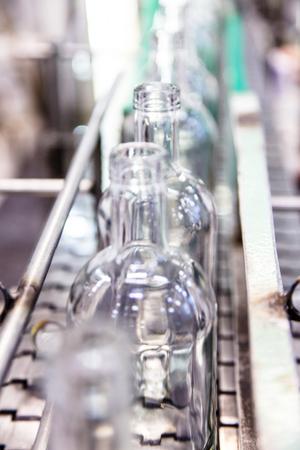 De flessen op de lopende band in de fabriek voor het bottelen van alcoholische dranken, Russische wodka.