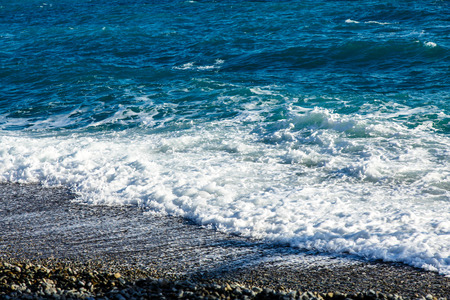 The waves rolled onto the beach of pebbles. Stock Photo