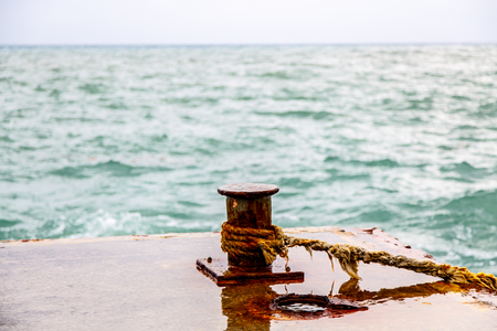 Old rusty bollards on the pier, the waves break on the jetty.