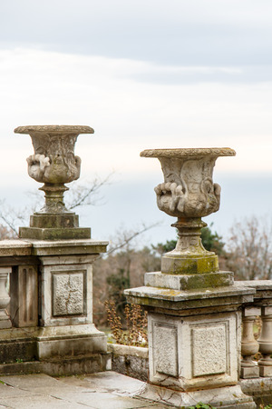 stands: Large stone flower vase stands on a ladder in the Park. Stock Photo