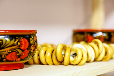 Russian dessert Sushka (drying) are on the shelf next to the bowls painted with Khokhloma ornament.