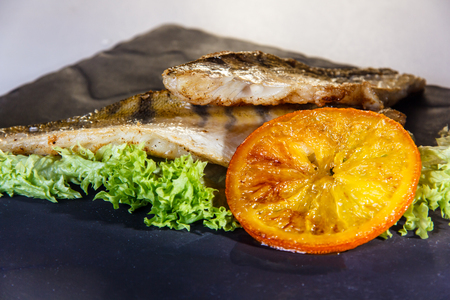 Fried fish (cod) with grilled orange lies on the plate. Stock Photo