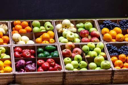 Apples, oranges, grapes, pears, and other fruits and vegetables lying on the counter of the store.