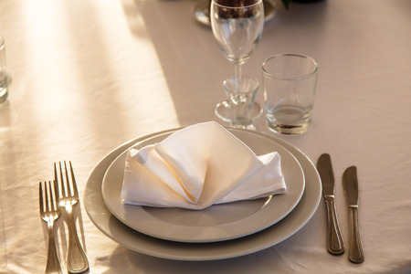 Linen napkin on a plate on the table covered with a white tablecloth. Stock Photo