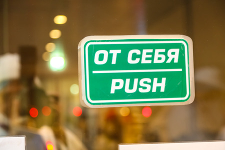 Sign Push In Russian And English On The Glass Door Behind Stock