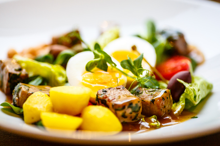 Salad with tuna, potatoes, capers, beans, egg and tomatoes.