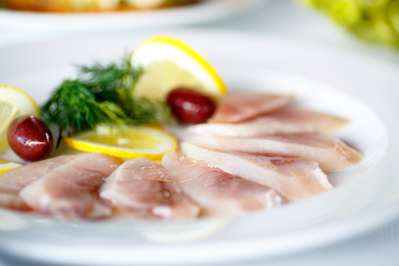Smoked or salted fish cut into thin slices with lemon on plate. Stock Photo