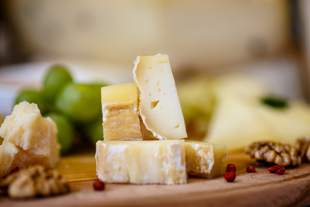 tabla de quesos: Different types of Italian cheeses (Parmesan, Gorgonzola, Roquefort) are on the Board. Macro.