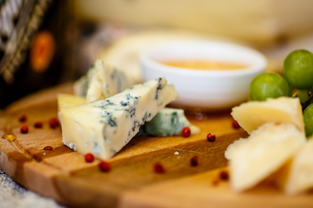 Different types of Italian cheeses (Parmesan, Gorgonzola, Roquefort) are on the Board. Macro.