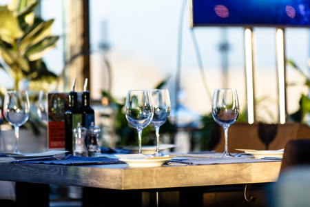 stands: Wine glass stands on the table in the restaurant. Evening, the setting sun. Stock Photo