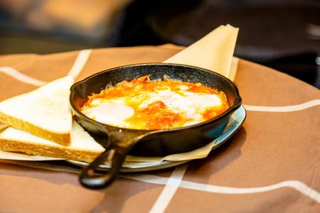 黒い鋳鉄製フライパンとトマトとスクランブルエッグ。お客様を見ないレストラン。