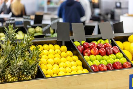 Lemons, apples and pineapples on the shelves in the supermarket
