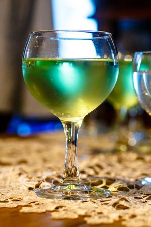 celebration: Green lemonade or cocktail in glass wine glasses.