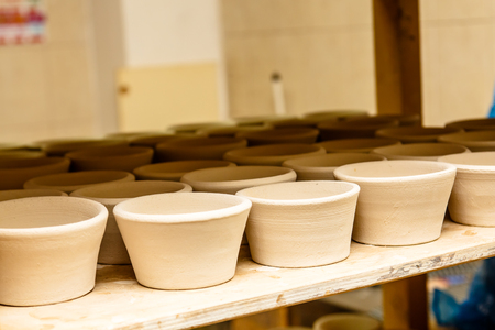 kitchen cabinets: A pottery. white bowls and plates are on shelves of the cupboard