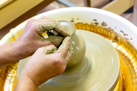 A pottery. Master on the circle makes a vase of clay.