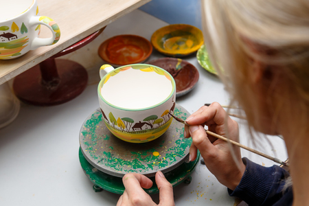 A pottery. The artist draws on the dishes and ornament drawings. Stock fotó - 86040317