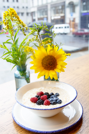 Oatmeal with berries with a yellow flower on the background of the rainy window.