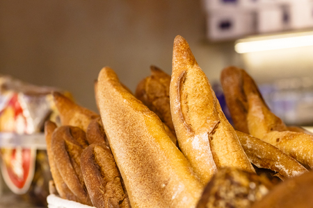 Homemade bread and a baguette lies in the basket on the counter of the store.