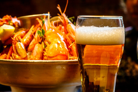 A glass of beer in the background is a plate of crab, shrimp, scallops, lobsters in the restaurant Banco de Imagens