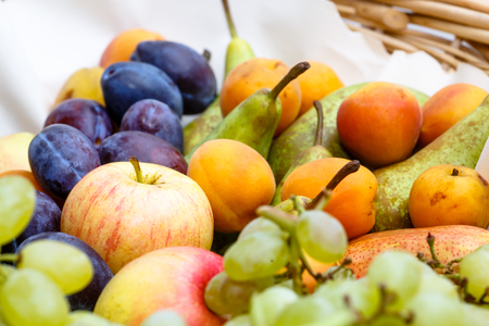 Wicker fruit basket: grapes, plums, bananas, apples, apricots, pears. Banque d'images