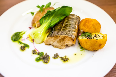 Fish baked with salad and potato croquettes. Stock Photo