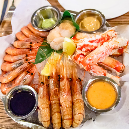 Crabs, shrimp, langoustines, scallops lay on a large platter.