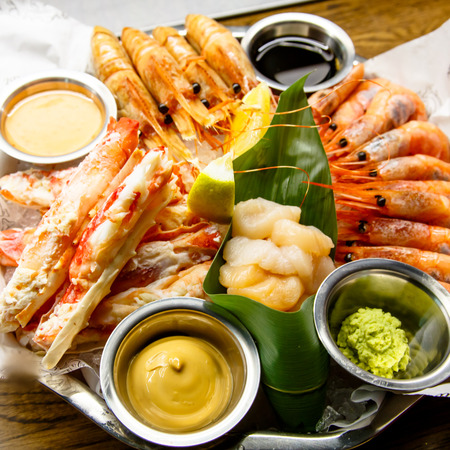 Crabs, shrimp, langoustines, scallops lay on a large platter. Stock Photo - 98037019