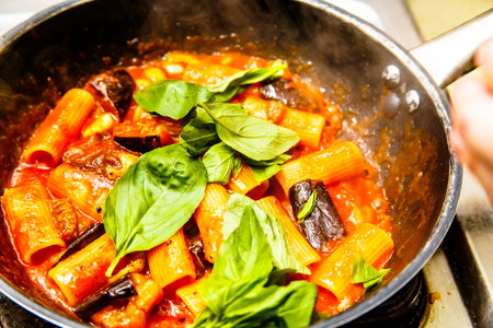 Cooking pasta (Rigatoni) with eggplant and tomato sauce in the restaurant kitchen. Stock Photo