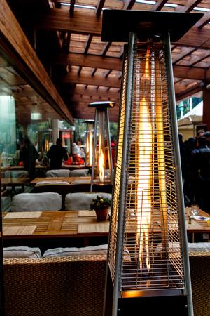Calentadores de gas en la terraza del restaurante, otoño, lluvia. Foto de archivo