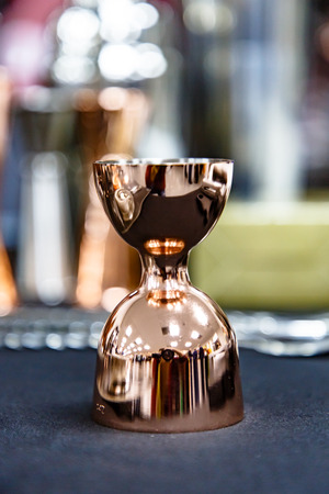 Copper jigger for cocktails is on the bar. Stock Photo