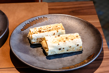The Shawarma is wrapped in pita bread two piece lies on a plate