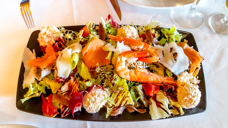 A large salad with shrimp, salmon and other fish is on the plate.