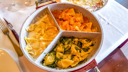 Three kinds of ravioli. with spinach, cheese and tomatoes are on the same plate