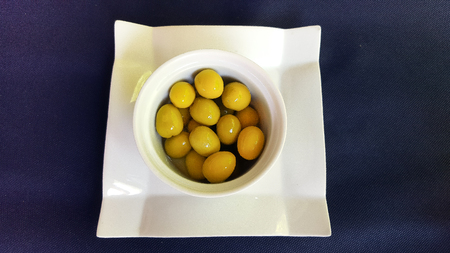Green olives lie in a white Cup.