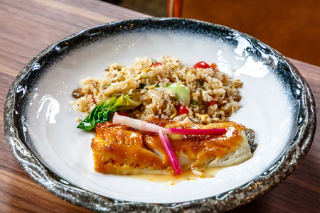 Baked fish with rice and vegetables is on a plate