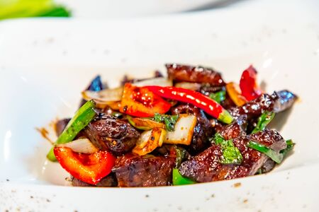 Chinese cuisine. Fried pieces of meat in pepper sauce with red pepper
