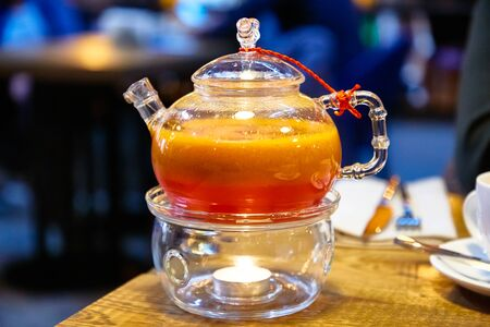 Red tea with sea buckthorn in a glass teapot. 写真素材 - 129477411