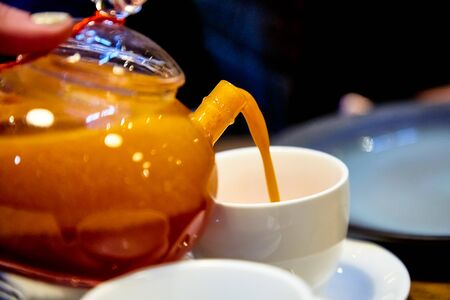 Red tea with sea buckthorn in a glass teapot. 写真素材 - 129477410