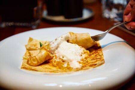 Crêpe avec garniture de viande et de fromage sur une assiette.