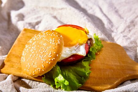 Burger with cutlet, tomatoes and egg is on a wooden Board